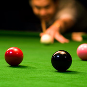 A snooker player about to pot the black
